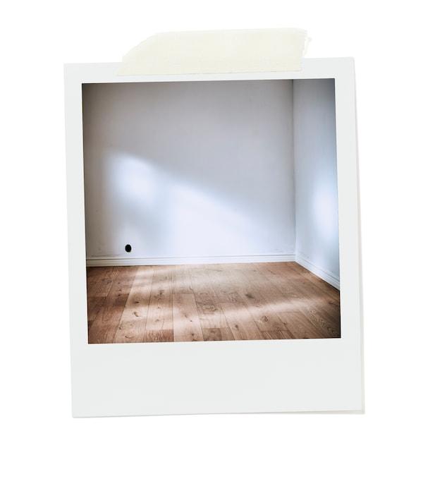 Coin ensoleillé d'une pièce vide aux murs blancs et nus, et au plancher en bois fait de larges panneaux nontraités.