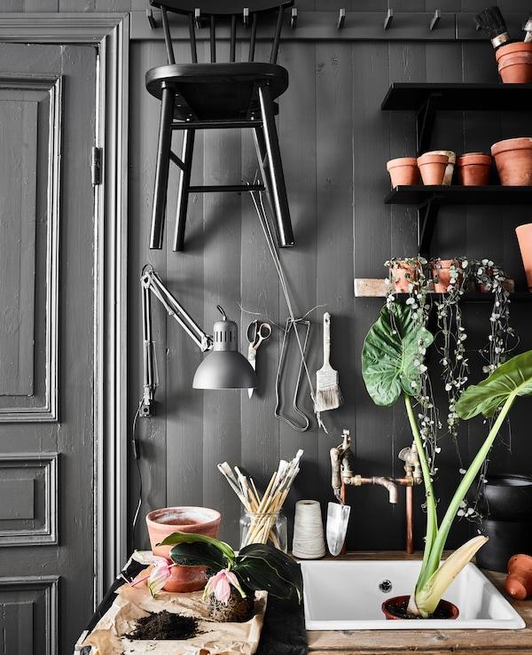 Coin jardinage dans une cuisine, avec nouvel évier, vieille table en bois collée au mur et étagères servant de rangement à des cache-pots et des ustensiles de jardinage