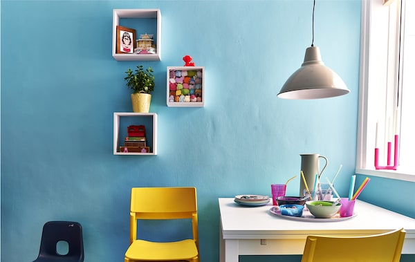 Coin repas avec murs bleus et chaises jaunes.