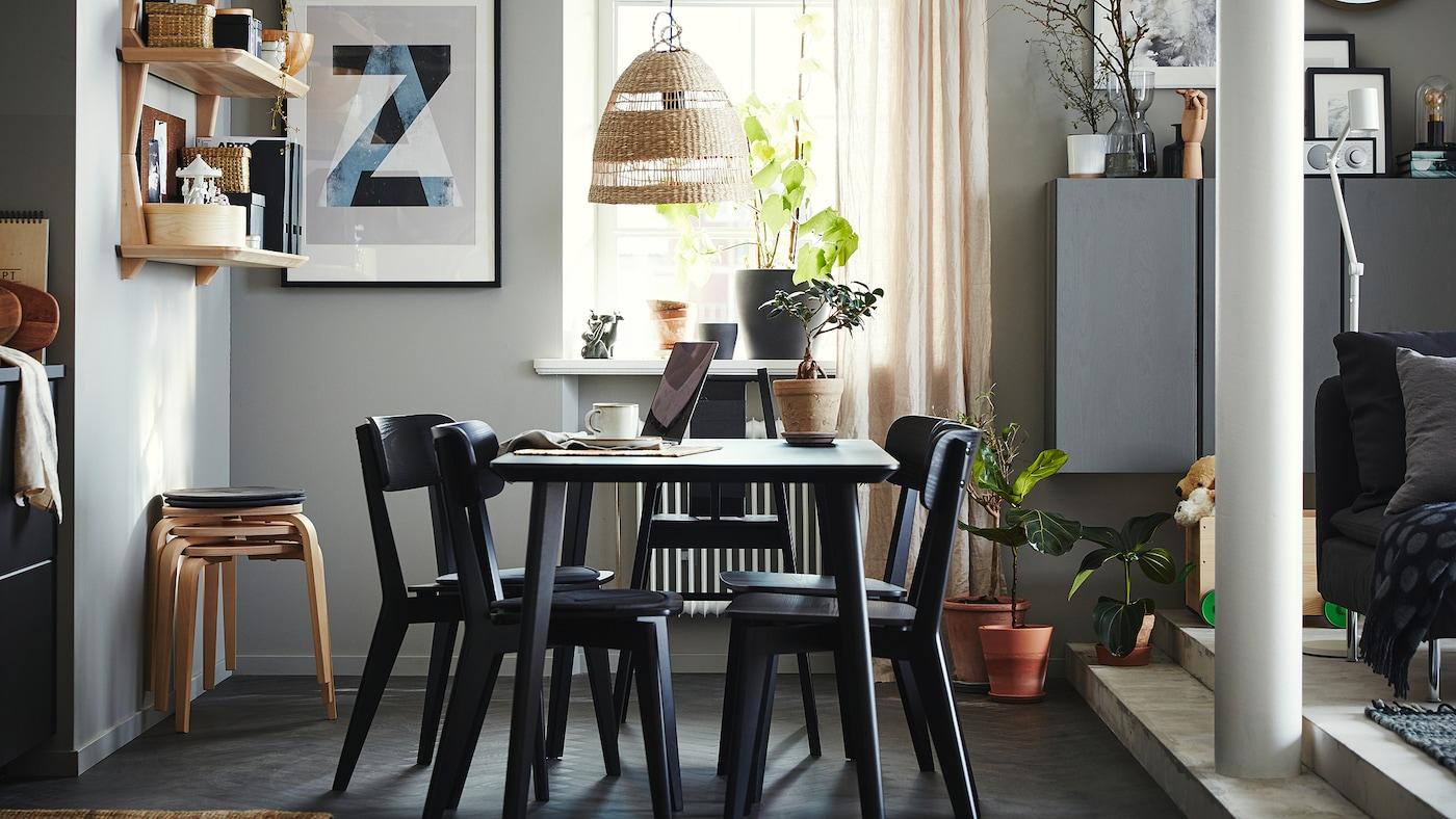 Coin repas avec une table, quatre chaises et une chaise haute en noir, des étagères en plaqué frêne, quatre tabourets et des rideaux beiges.