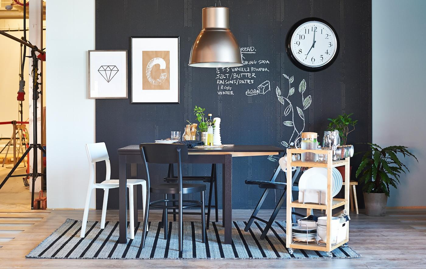 Coin repas devant un mur noir avec vaisselle et petit déjeuner posés sur une desserte