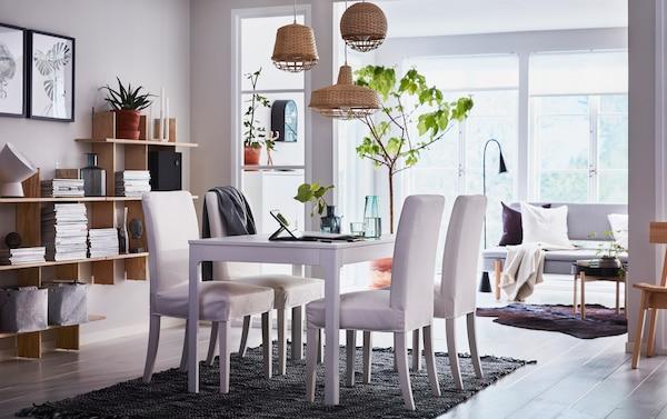 Coin repas en beige, noir et blanc dans un séjour décloisonné, avec chaises rembourrées HENRIKSDAL blanches et table extensible EKEDALEN.