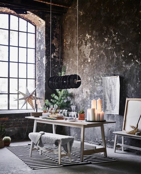 Coin salle à manger du loft au look industriel avec une table présentant un buffet et un banc garnie d'un jeté.