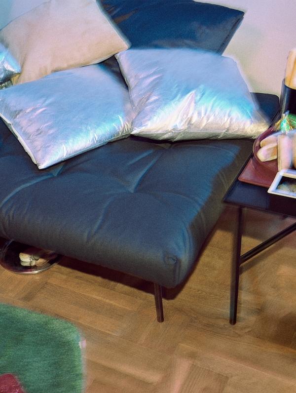 Coixins de color plata i beix que repel·leixen l'aigua, a sobre d'un reposapeus IKEA FREKVENS de color negre.