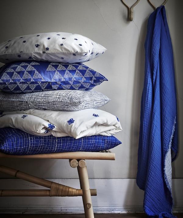 Cojines TÄNKVÄRD con estampado azul y blanco apilados sobre un banco de ratán y un trozo de tela azul colgado de un gancho.