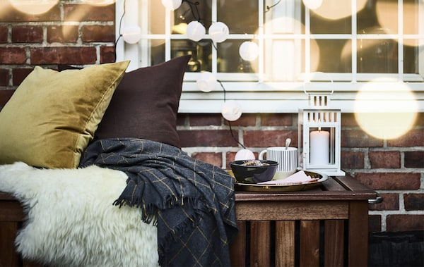 Cojines y colchas, una bandeja con un cuenco y una taza y un farolillo sobre un banco en el exterior de una ventana con una guirnalda.
