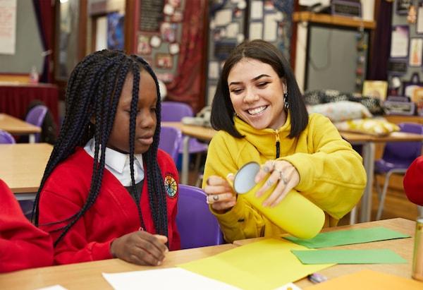 Colaboradora de IKEA ayuda a una niña con uniforme con una manualidad utilizando papel de color.