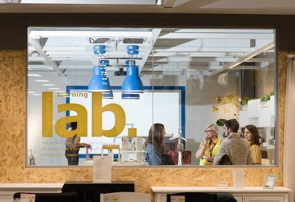 Colaboradores de IKEA hablan a los clientes detrás de una ventana con «learning lab» escrito en el cristal.