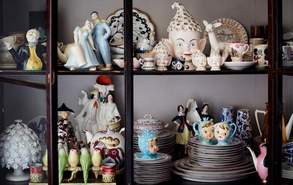 Colección de adornos de porcelana en un armario con puertas de vidrio.