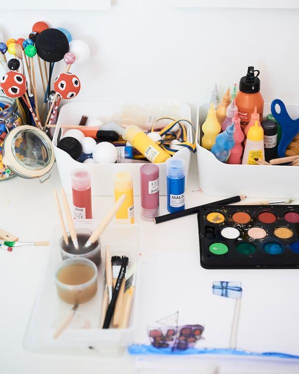 Colección de cajas de plástico blanco para organizar pinturas, pinceles y otros materiales para las manualidades en un escritorio.