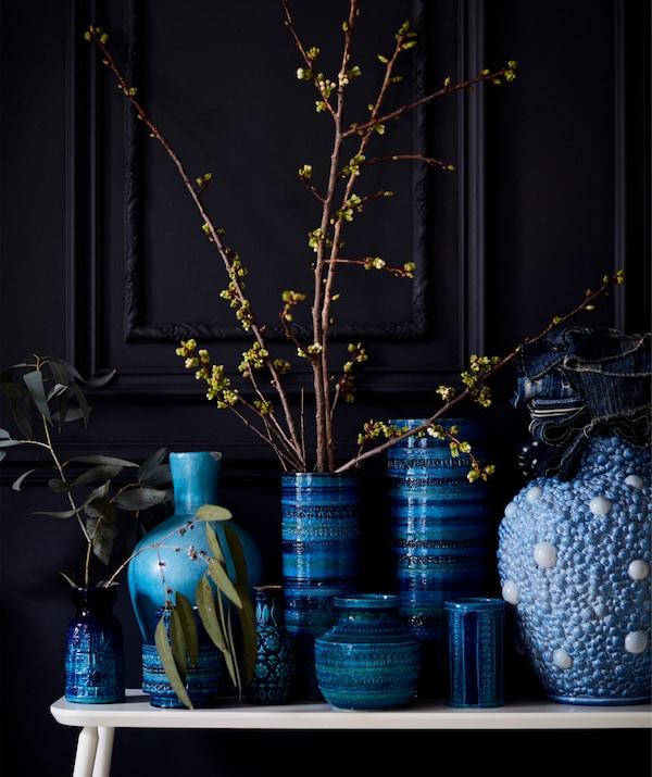 Colección de jarrones azules sobre un banco blanco.
