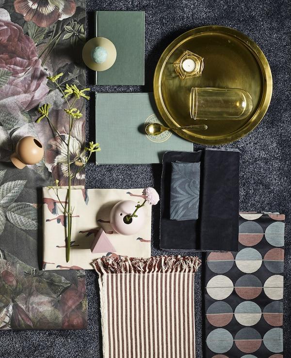 Colección de objetos decorativos en tonos verde, rosa y bronce colocados en una alfombra rectangular ÅDUM azul oscuro.