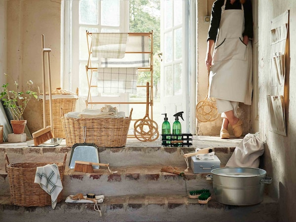 Colección de productos BORSTAD colocada junto a una puerta de entrada iluminada por el sol; a su lado, una mujer sostiene el sacudidor de alfombras.