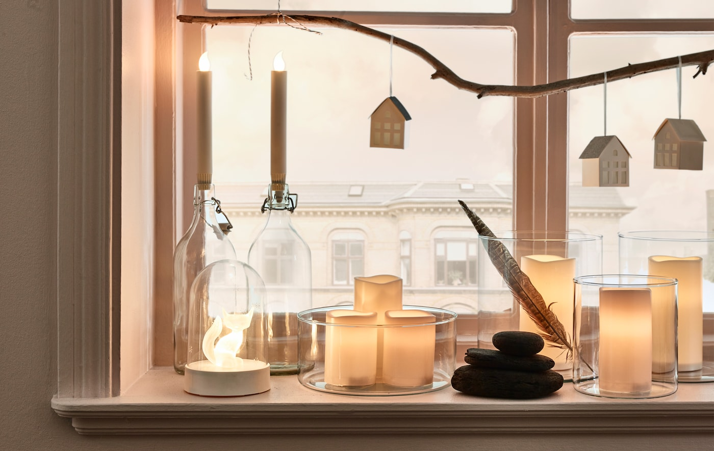 Colección de velas LED con batería LJUSANDE y velas grandes LED GODAFTON en floreros de cristal al lado de una ventana.