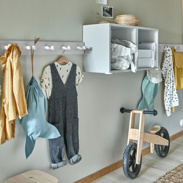 Colgadoiros con ganchos brancos montados na parede, con roupa de nenos colgada, estantes gris claro e bicicleta infantil de madeira.