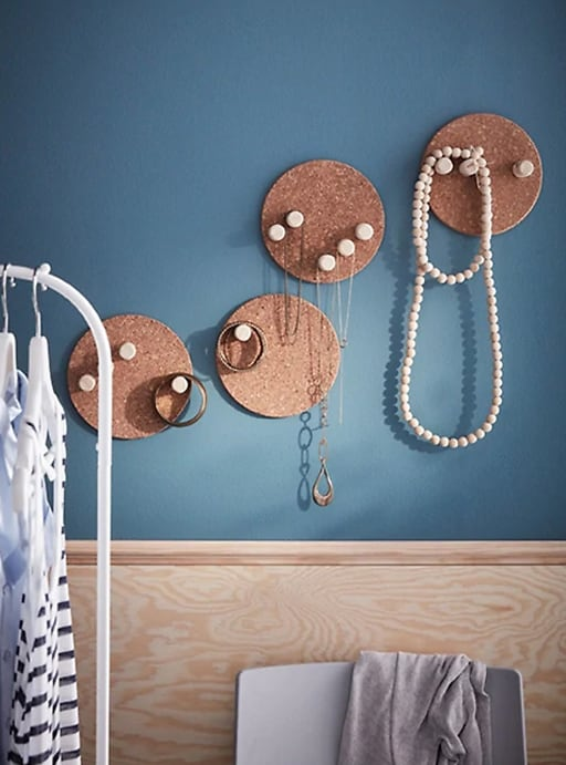 Colgadores de joyas hechos con corchos sobre una pared azul.