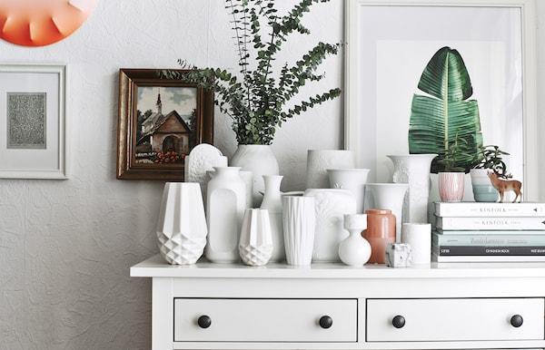 Collection de vases blancs sur une commode.