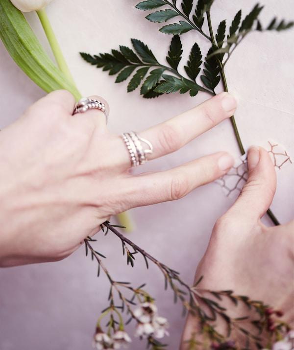 Colocación de un ramo de flores en una pared blanca con cinta adhesiva con estampado monocromo.