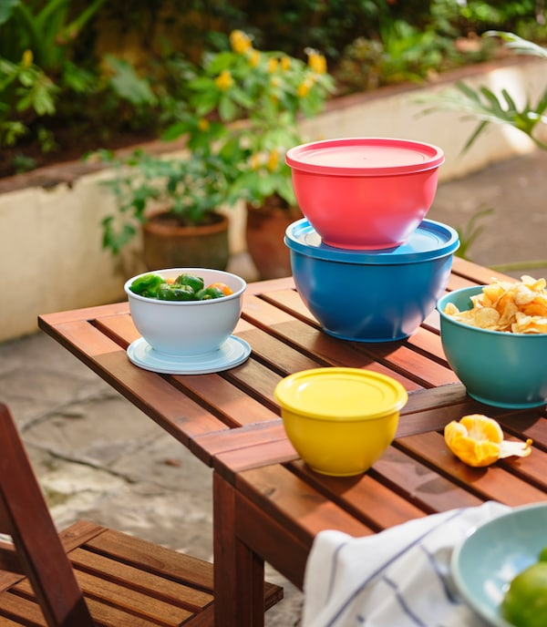 Colorful bowls with lids placed sporadically on a wooden table in an outdoor space. Plants stand in the background.