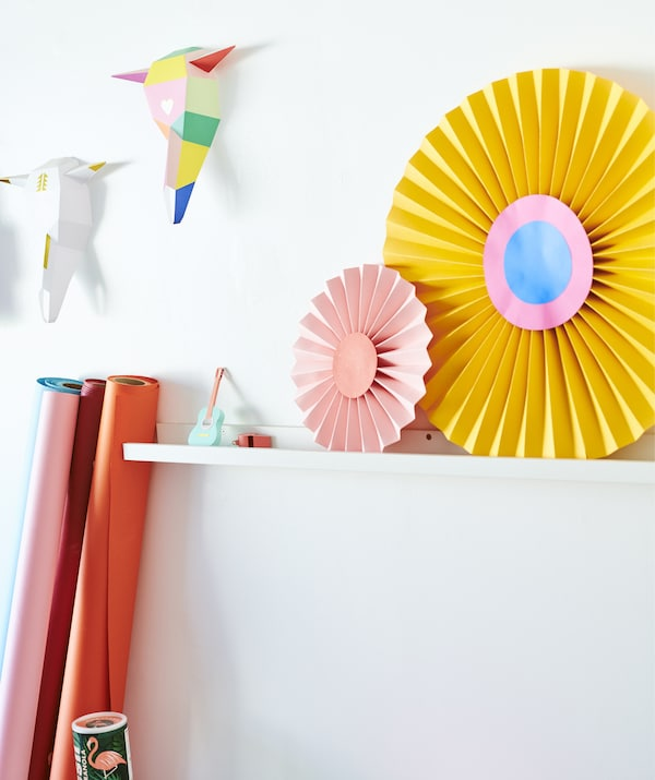 Colorful paper shapes displayed on a white picture ledge on a white wall.