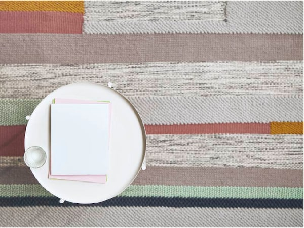 Colour rug with coffee table on top. Coffee mug and notebook on table.