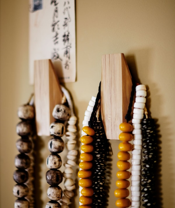 Colourful beaded necklaces hanging from two wooden hooks.