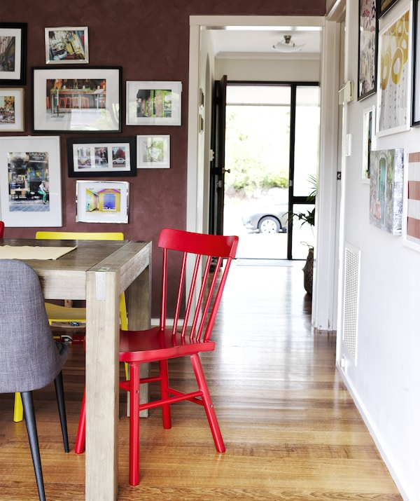 Colourful chairs around a wooden table and a dark red wall with picture gallery.