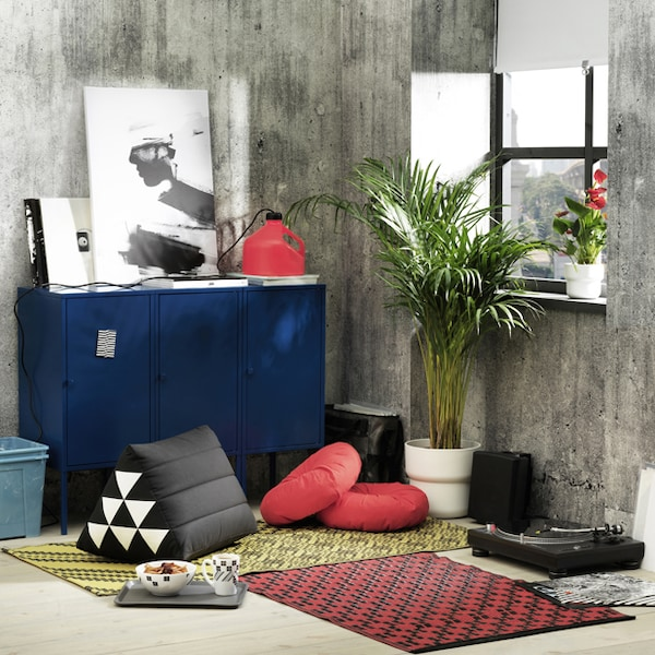 Colourful cushions and accessories from the SAMMANKOPPLA collection, in a room with concrete walls.