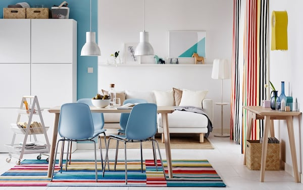 Colourful open plan dining and sitting room with LISABO light wood table and BRORINGE-LEIFARNE blue chairs.