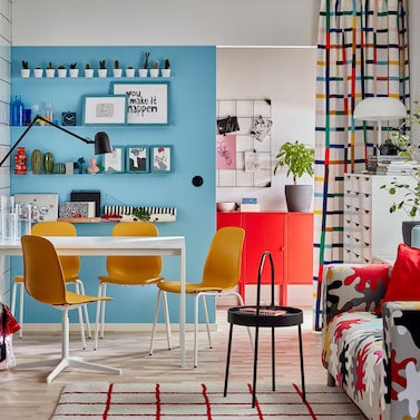 Colourful small home with yellow chairs and a white table. The curtains, rug, sofa and kitchen doors have various patterns.