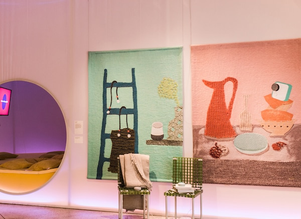 Colourful tapestries depicting homewares and a round mirror on a wall.