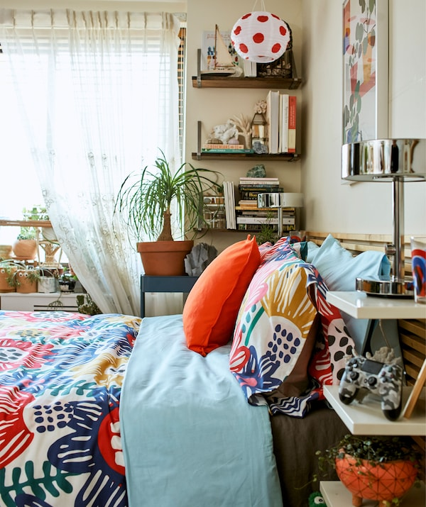 Colourful textiles on a bed with storage on the headboard and wall shelves.