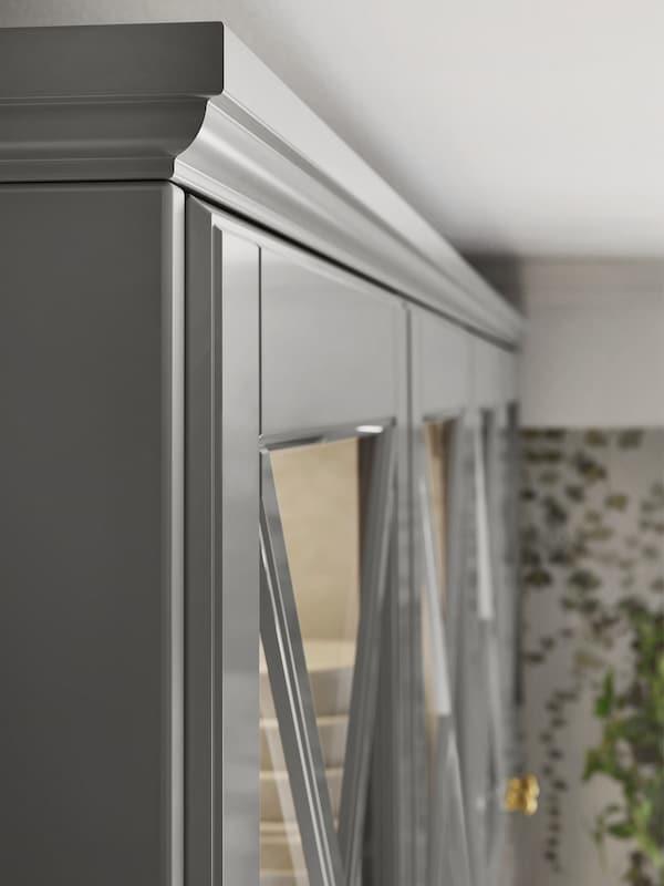 Colțul de sus al unui rând de dulapuri de bucătărie cu uși de sticlă și un mulaj decorativ conturat deasupra.