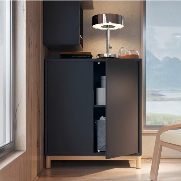 Combinação de armário EKET em cinzento escuro com pernas e prateleira amovível, com um candeeiro em cima e uma janela ao lado com uma vista panorâmica.