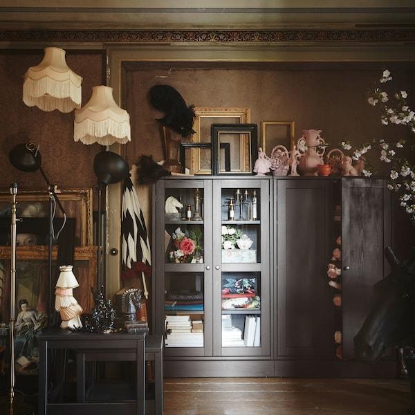 Combinación de almacenaxe HAVSTA en marrón escuro con portas de vidro e outras pezas da serie mesturadas con artigos vintage.