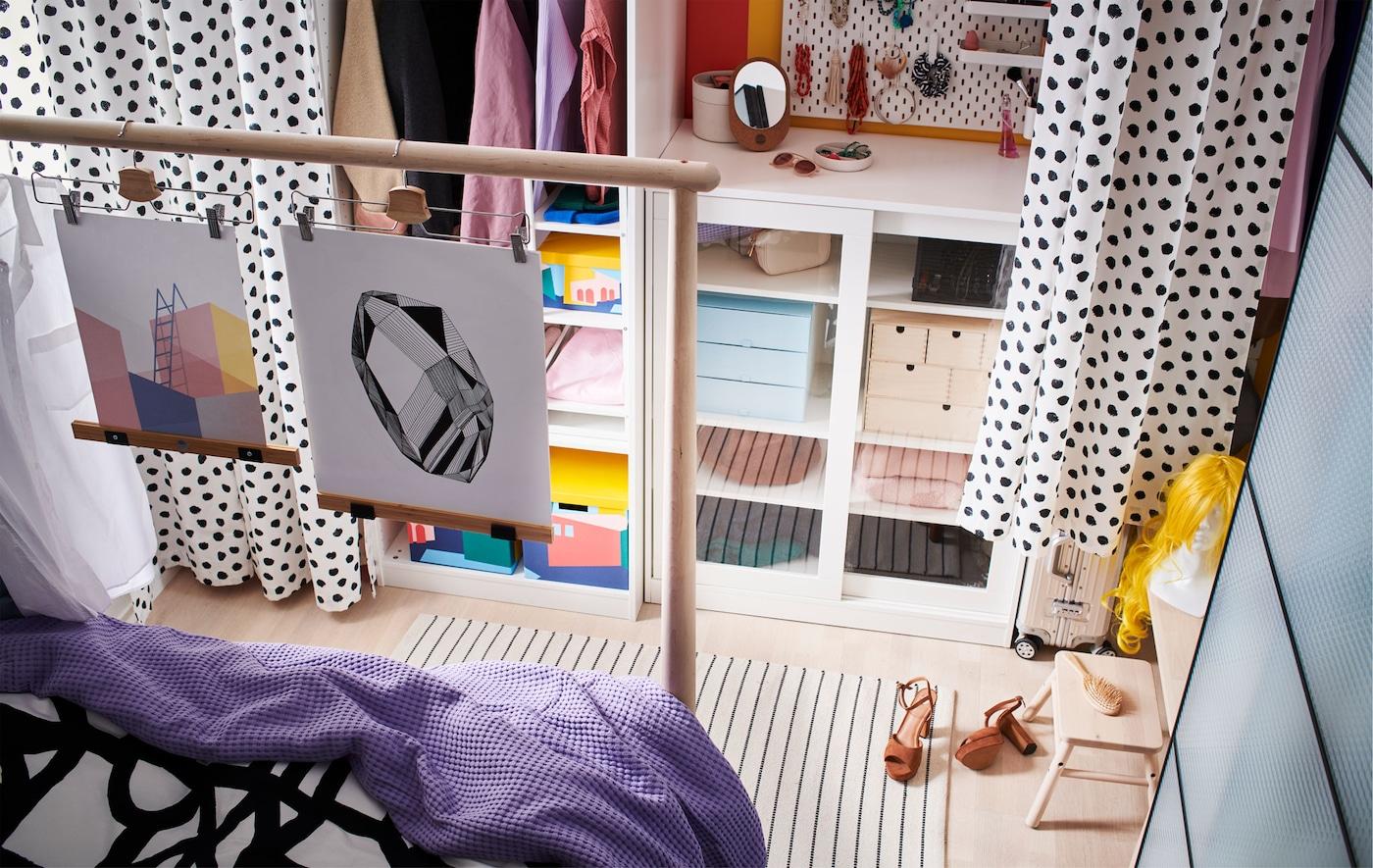 Combinaison de rangements ouverts et fermés le long d'un mur, avec passage entre des rideaux suspendus et le pied du lit.