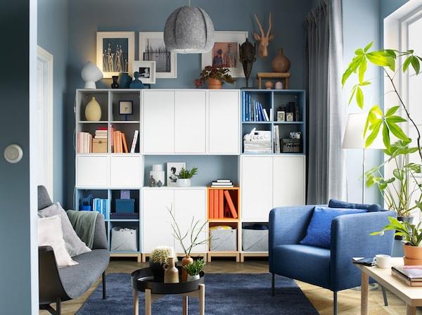 Combinaison de rangements ouverts et fermés multicolore EKET sur pieds couvrant le mur d'un salon en noir, bleu, gris et blanc.