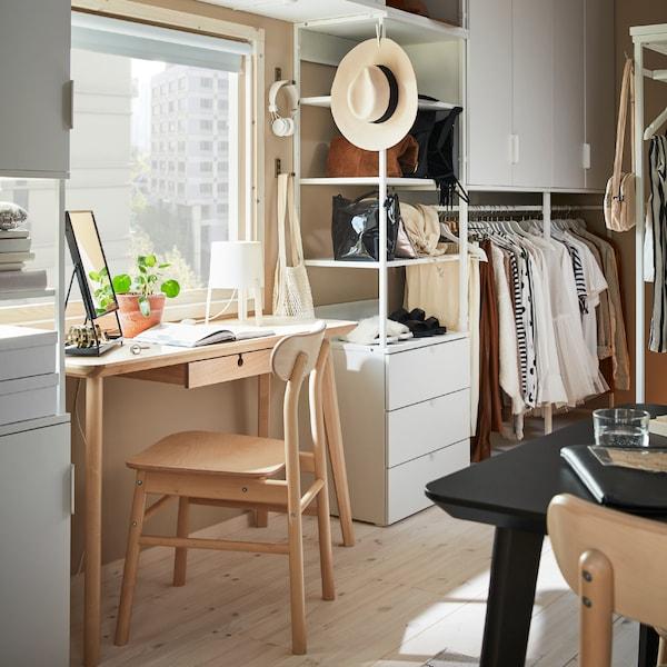 Combinaison de rangements PLATSA blancs, avec des papiers et des vêtements, près d'un bureau LISABO et d'une chaise RÖNNINGE en bouleau.
