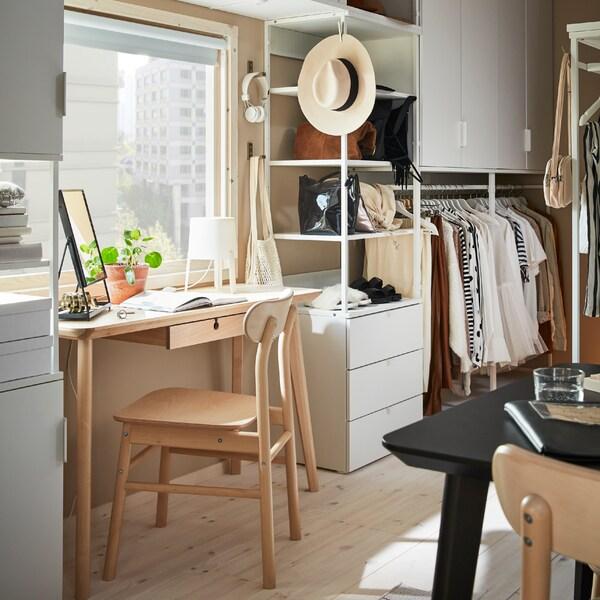 Combinazione con sistema PLATSA bianco con cancelleria e vestiti, attorno a un tavolo in betulla LISABO e a una sedia RÖNNINGE.