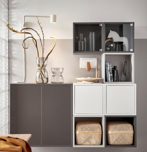 Combinazione di mobili EKET bianchi e grigi con due scatole con coperchio SMARRA, due vasi in vetro e oggetti personali.