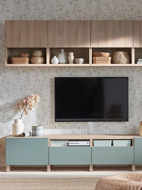 Combinazione mobile tv composto da elementi bassi in legno chiaro con quattro cassetti con frontale turchese. Sospesi sulla parete, sopra la tv, altri quattro elementi in legno chiaro con una parte a giorno e una con antina dello stesso colore.