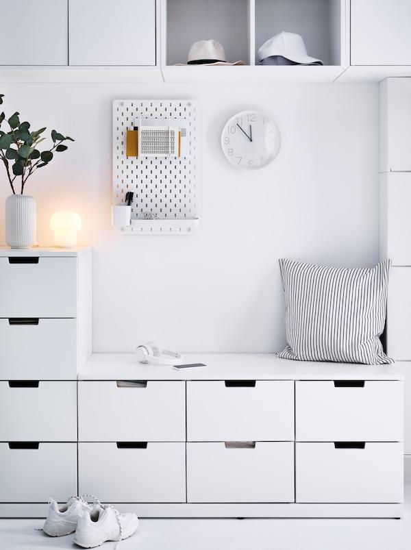 Combinazione per l'ingresso composta da cassettiere NORDLI bianche con quattro e sei cassetti, che fanno anche da panca.