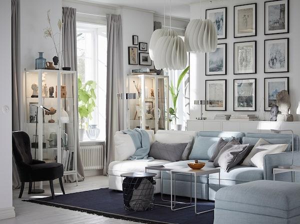 Combine as capas do sofá modular VALLENTUNA, em branco e azul claro, e crie uma sala personalizada de acordo com o seu estilo. Acrescente molduras HOVSTA para criar uma galeria de parede e use as vitrinas MILSBO para expor o que mais gosta.