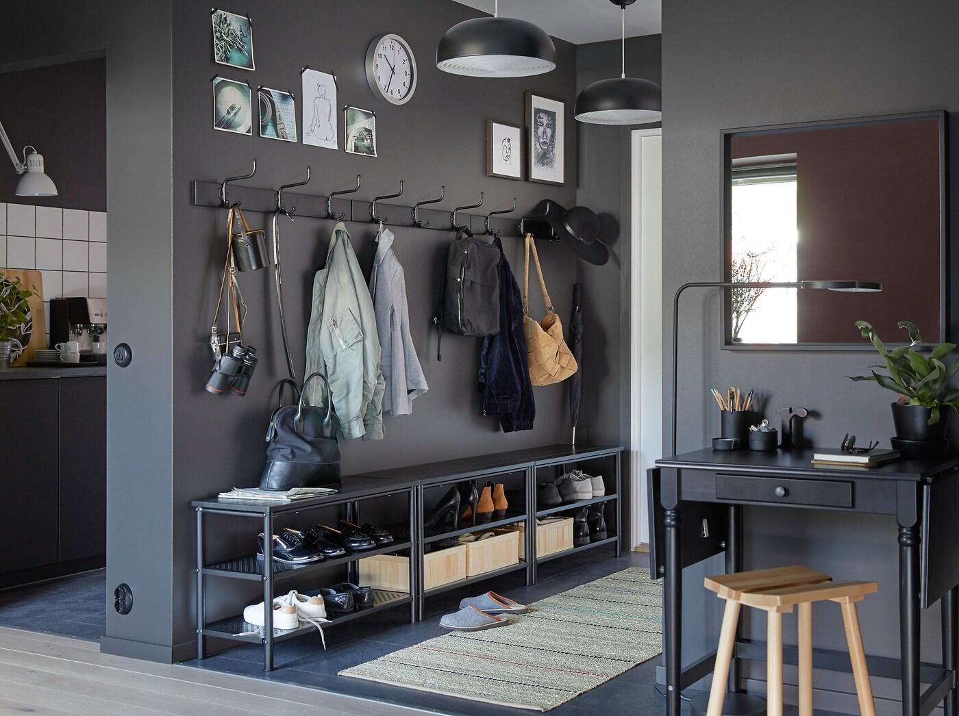 Combineer drie zwarte PINNIG schoenenrekken en drie PINNIG rekken met haken op een rij tegen een donkergrijze muur om veel opbergruimte te creëren in een smalle hal