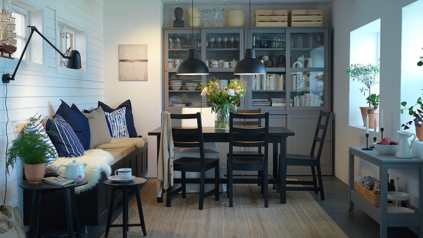 Comedor cunha mesa e cadeiras negras, unha alfombra de xute, lámpadas colgantes negras e unha combinación de almacenaxe con portas corredizas.