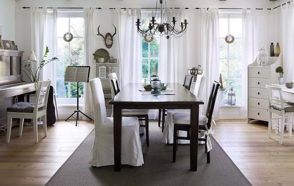 Comedor grande de estilo rústico con una mesa oscura y sillas blancas con cojines. Una alfombra grande y oscura divide el espacio.