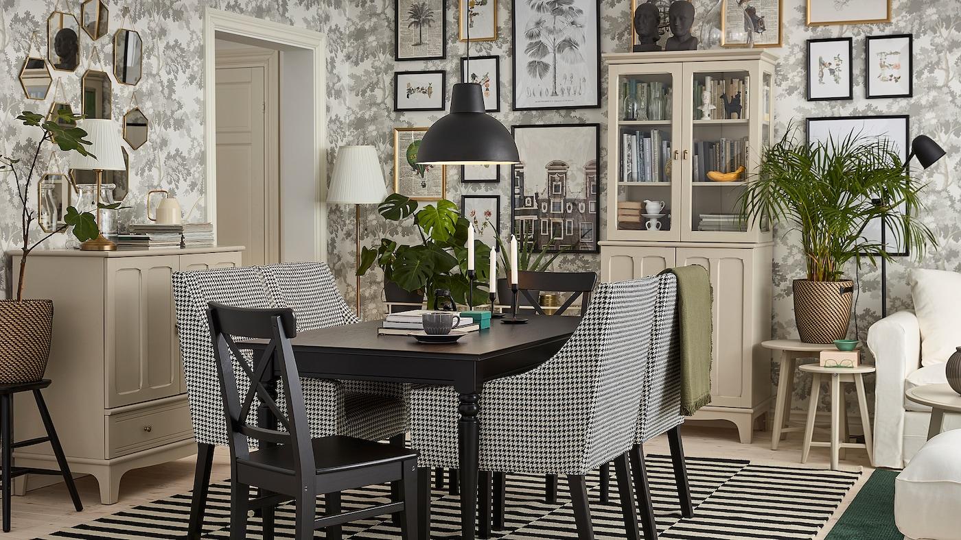 Comedor tradicional cunha mesa negra, armarios en beixe claro, cadeiras negras, cadeiras de brazos brancas e negras e unha alfombra de raias.