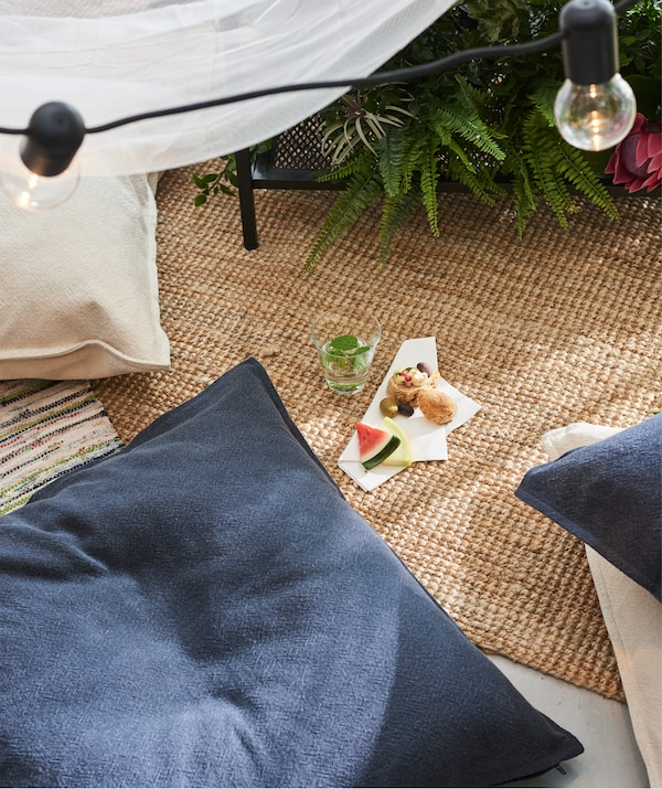 Comfy JOFRID cushions with blue and tan covers on a woven floormat in a living room