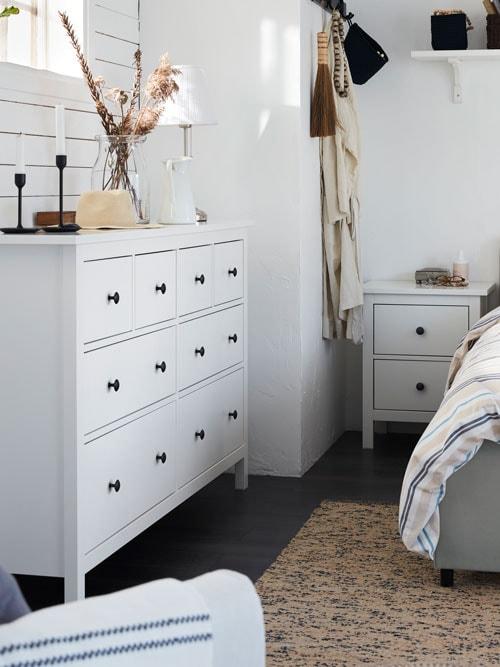 Commode à huit tiroirs HEMNES blanche placée sous une fenêtre, près d'un lit HAUGA dans une chambre à coucher minimaliste de style rustique.