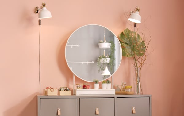 Cómoda cinzenta com puxadores em pele, com um espelho branco redondo em cima e uns candeeiros brancos de parede para iluminação.
